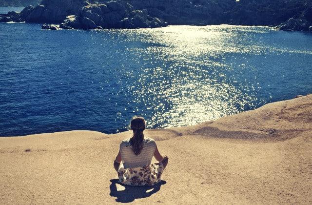 Meditation lernen - junge Frau meditiert am Meer