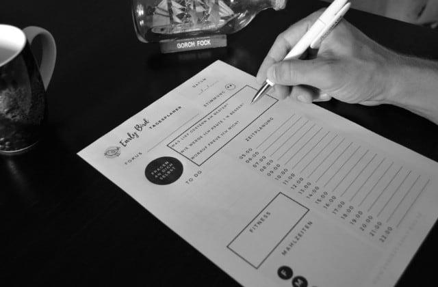 Tagesplaner - Zettel und Stift in einer Hand