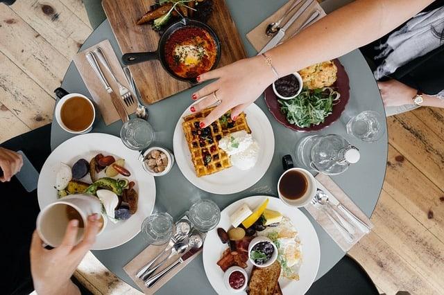 Eiweißreiches Frühstück - Menschen am Frühstückstisch mit verschiedenen Lebensmitteln
