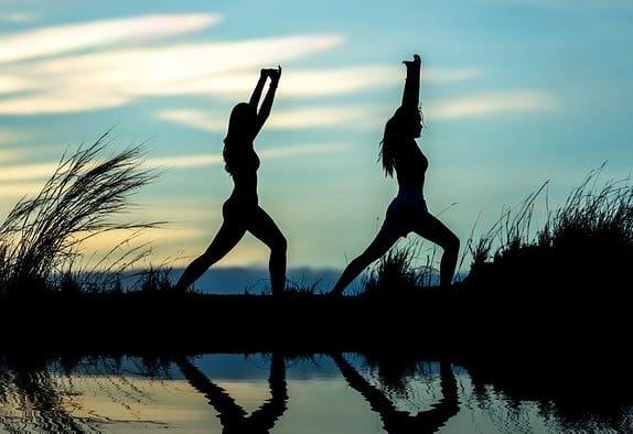Morgengymnastik - zwei junge Frauen machen Sport am See